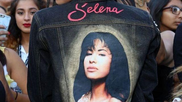 Una mujer usa una chaqueta con la imagen de Selena en la espalda.