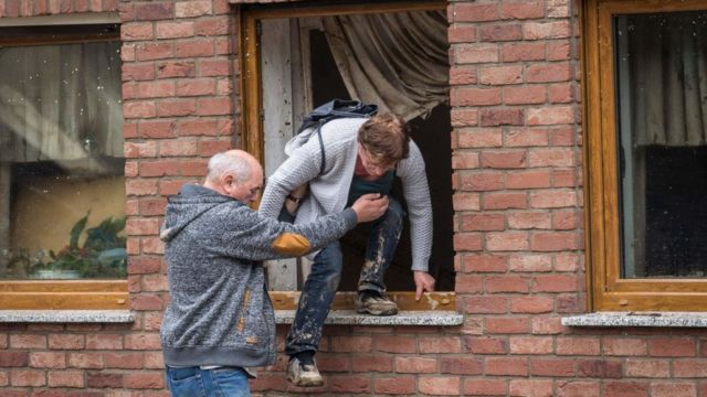 Un hombre ayuda a una mujer a trepar por una ventana tras las importantes inundaciones en Schuld