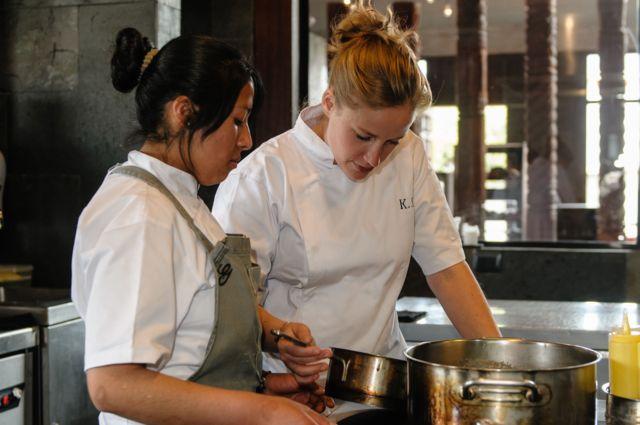 Chef le muestra el contenido de una olla a una estudiante de cocina