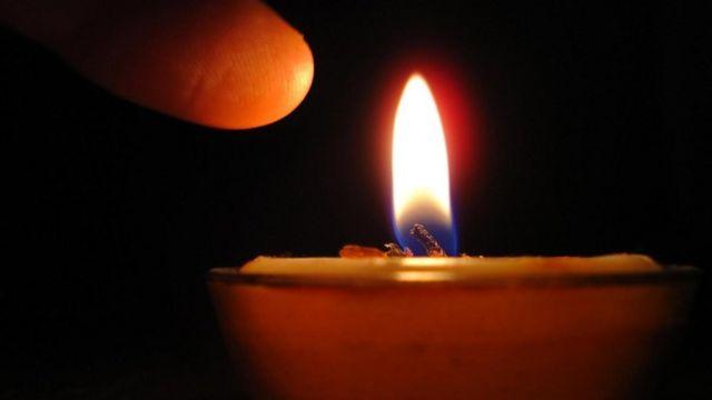 Una persona a punto de tocar la flama de una vela
