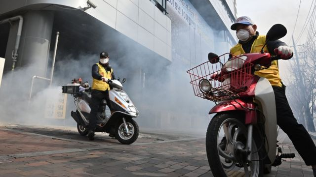 當局在大邱市爆發集體感染的教會附近噴灑消毒劑。