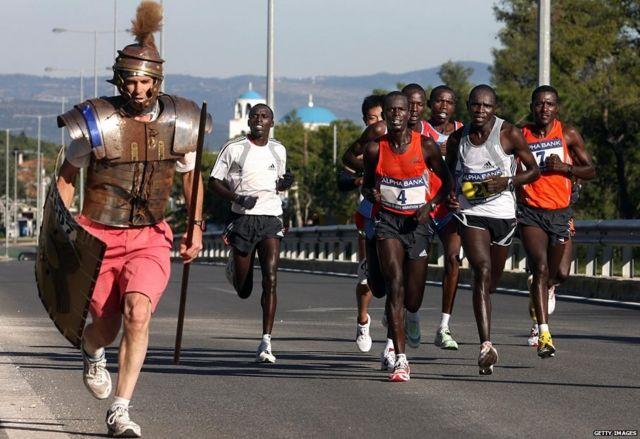 Tom Podesta de EE.UU. corriendo vestido como un antiguo soldado griego al lado de un grupo de atletas liderados por el ganador de la Maratón Clásica de Atenas de 2006, el keniano Henry Tarus.