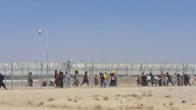 Afganos caminan entre las vallas en la frontera entre Afganistán y Pakistán