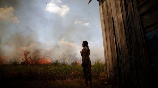 Mulher do lado de fora de casa observando floresta queimando ao fundo