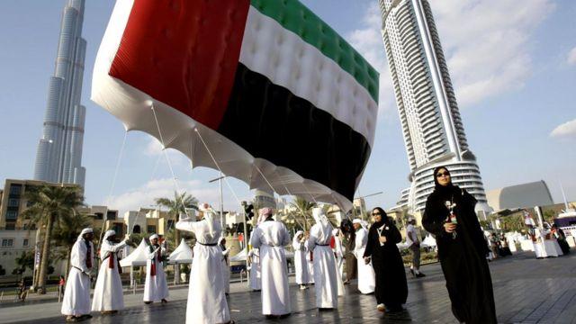 Жители несут государственный флаг перед самым высоким в мире небоскребом - башней Бурдж-Халифа - во время торжеств по случаю Национального дня ОАЭ (Дубай)