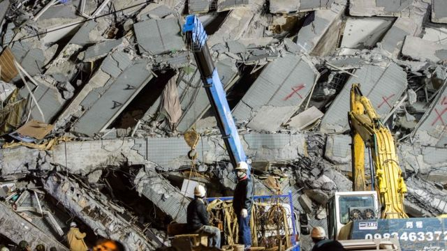 Rescue workers inspect the scene of a collapsed building in the southern Taiwanese city of Tainan following a strong 6.4-magnitude earthquake that struck early on February 6