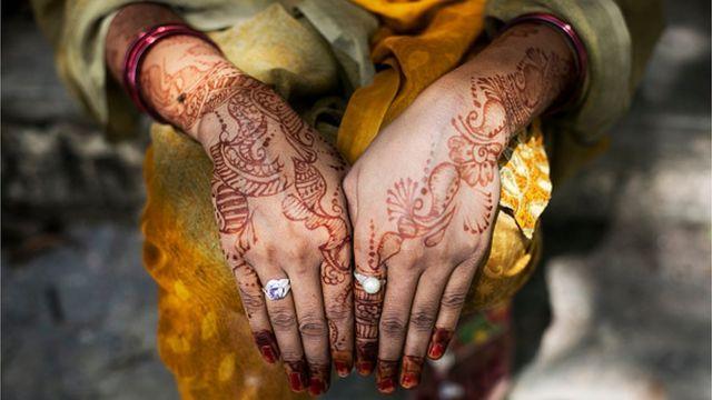 Uma mulher indiana com mãos pintadas de hena