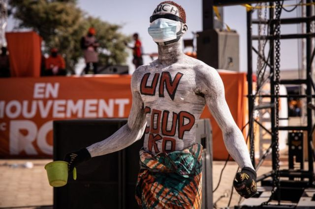"A man walks at a rally with the words ""un coup KO"", meaning ""a knockout blow"", painted on his torso."