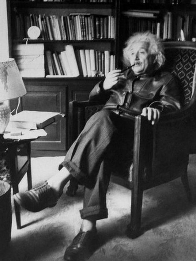 Albert Einstein sentado, fumando y sin medias.