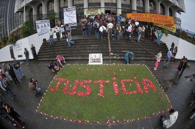 """Familiares de las víctimas de la masacre de Dos Erres, en Petén, Guatemala, escribieron """"justicia"""" con pétalos de flores a la entrada de la Corte Suprema de Justicia durante el juicio por el caso el 2 de agosto de 2011."""