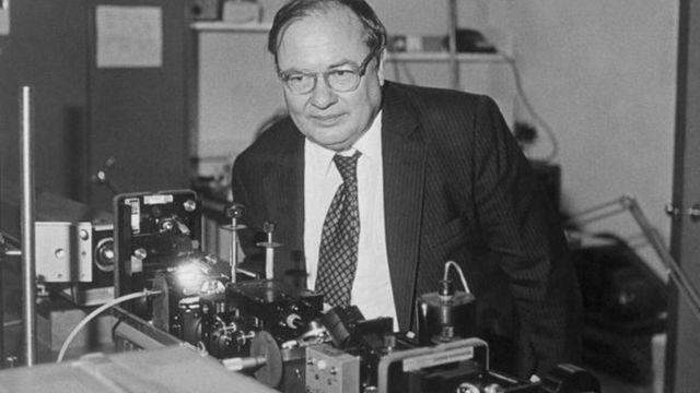 Arthur Schawlow posando com laser em um laboratório em Stanford, Estados Unidos