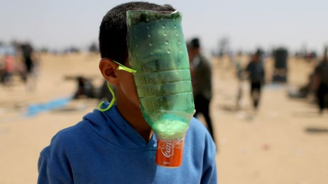 طفل صنع قناع على وجهه من زجاجة بلاستيكية