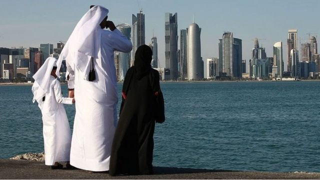 A man and two children in traditional dress stare across water at a city in the Persian Gulf