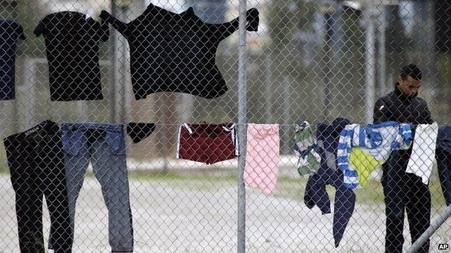 A migrant stands near clothes hanging on a fence at a former Olympic indoor stadium in southern Athens, which is being used as a temporary shelter