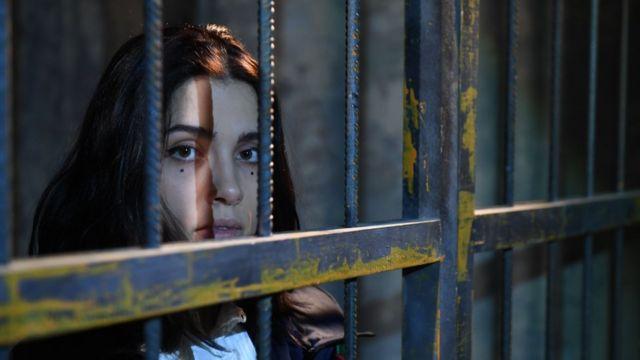Участница Pussy Riot Надежда Толоконникова за решеткой во время перформанса.