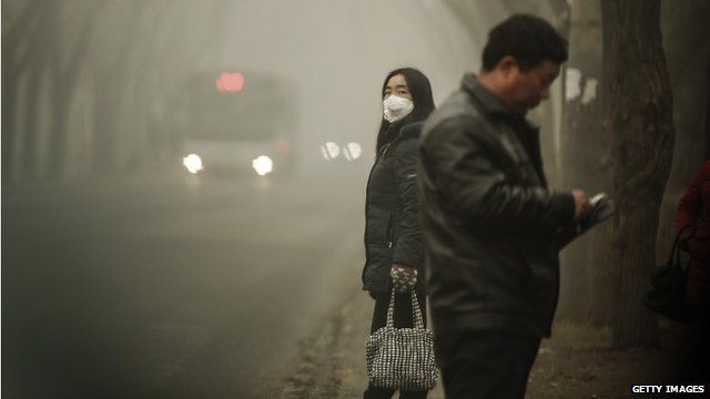 A woman wears a face mask next to traffic shrouded in heavy smog on December 1, 2015 in Beijing