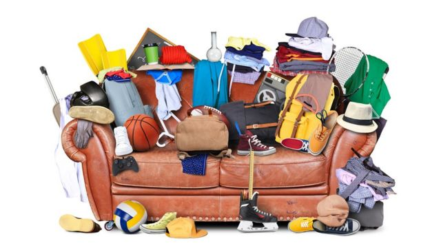 A messy sofa covered in clothes, shoes and other random objects.
