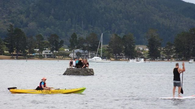 New Year revellers enjoy a drink on a special sand island they constructed earlier in the Tairua estuary on the Coromandel peninsula