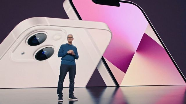 Apple CEO Tim Cook during a presentation on the background of a snapshot of the iPhone 13