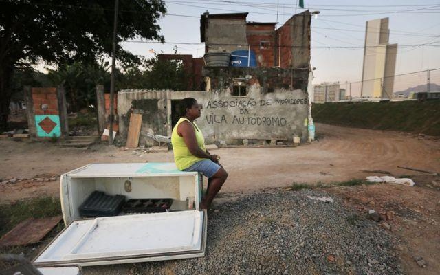 Mujer sentada sobre un refrigerador en desuso en una favela de Brasil.