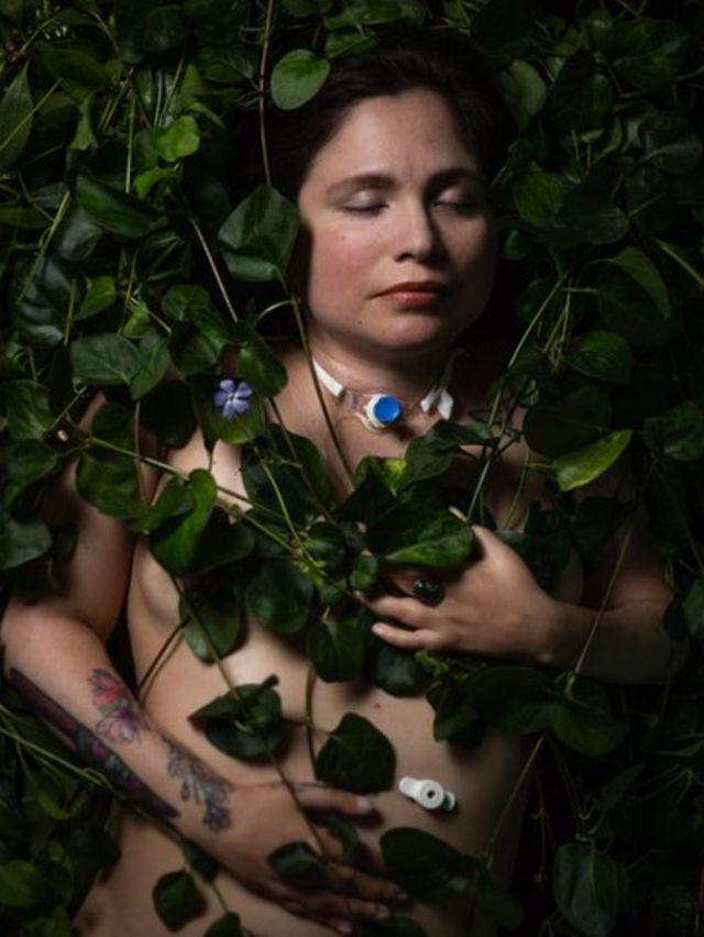 Ana Estrada rodeada de hojas verdes