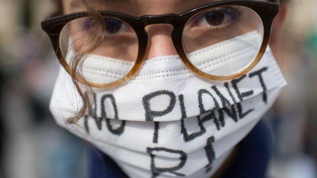 """Una joven con una mascarilla que dice """"no hay planeta B"""""""