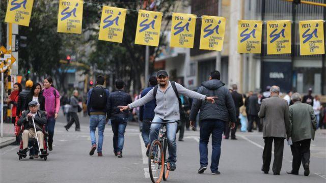 """Un hombre en monociclo bajo carteles a favor del """"sí"""" en Colombia."""