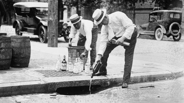 Agentes derraman alcohol incautado por una alcantarilla, cerca de 1921