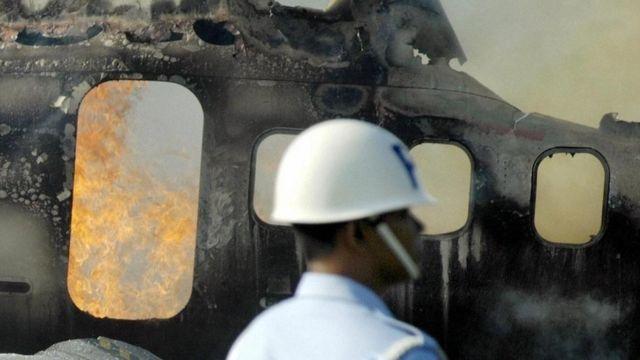 Una persona de equipos de rescate frente al fuselaje de un avión quemado