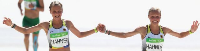 Anna Hahner (L) and her sister Lisa holding hands as they approach the finish line