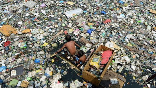مردی در میان زبالههای پلاستیکی