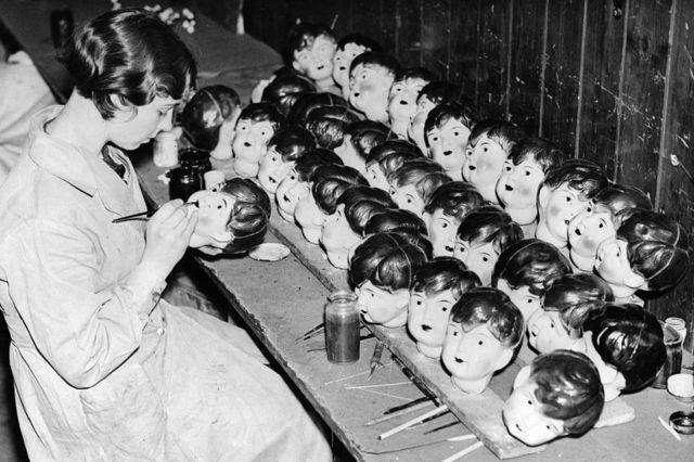 Сотрудница фабрики в Лестере расписывает лица целлулоидных кукол, 1935 год