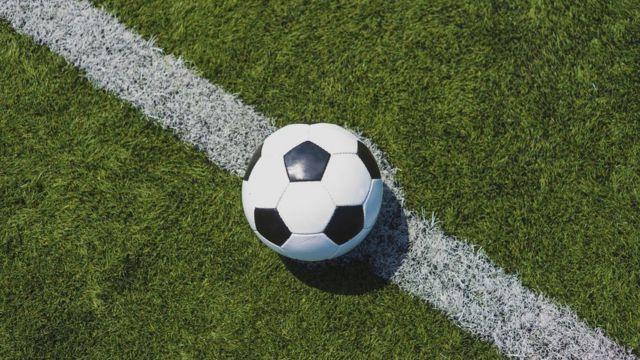 Bola sobre linha em capo de futebol