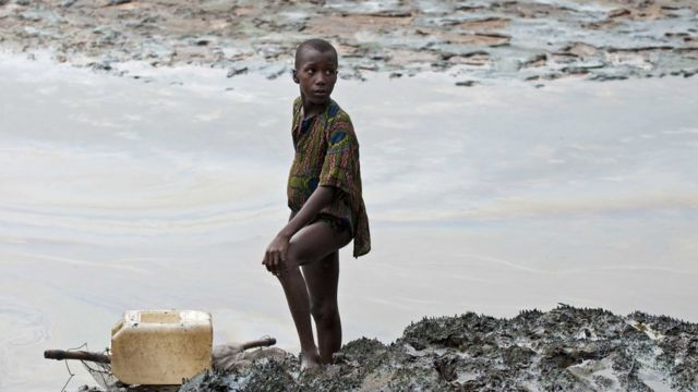 A boy with a fishnet standing on the oil stained bank of a creek near Goi, Ogoniland, Nigeria