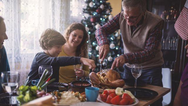 Avô corta o Peru e distribui para a família durante um almoço de Natal