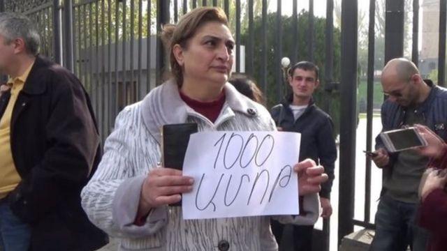 """Parlamentin qarşısında keçirilən etiraz aksiyasında qadın """"1000 dram (vermək) ayıbdır"""" şüarını tutur"""