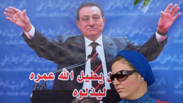 إحدى مؤيدات مبارك أمام ملصق تأييد له في عيد ميلاده خارج المستشفى حيث كان يعالج