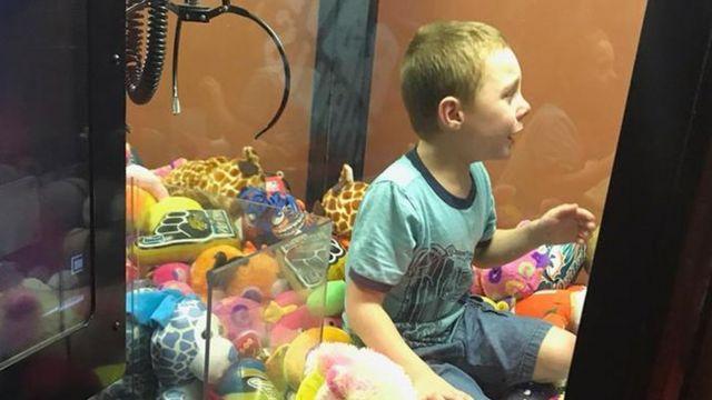 پسربچه در داخل ماشین اسباب بازی شانسی نشسته است