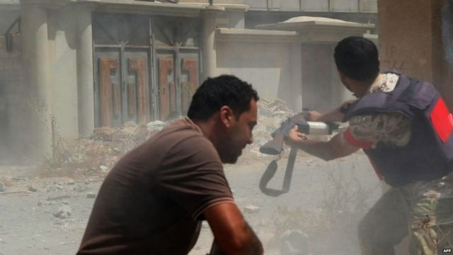 Pro-government fighters fire their weapons in the city of Sirte, Libya