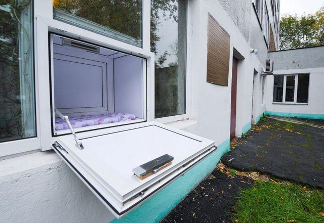 Uma caixa com porta aberta e pequeno colchão no interior de construção