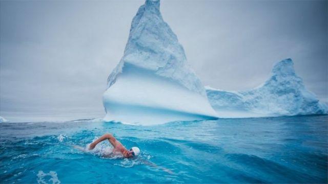 لويس بيو يسبح بالقرب من جبل ثلجي