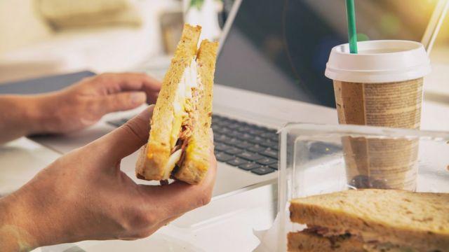 Mão segurando sanduíche e, ao lado, copo de café
