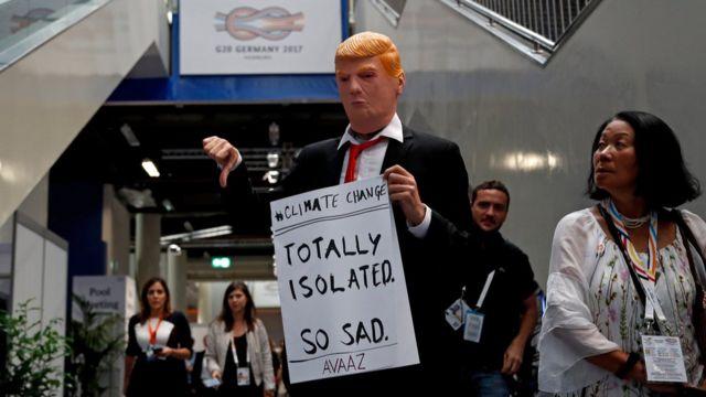 漢堡G20峰會會場內一名男子帶起特朗普面具並舉起調侃他因氣候變化問題遭到孤立的標語牌(9/7/2017)