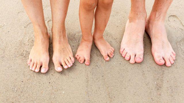 Tres pares de pies, dos de adulto y uno de niño.