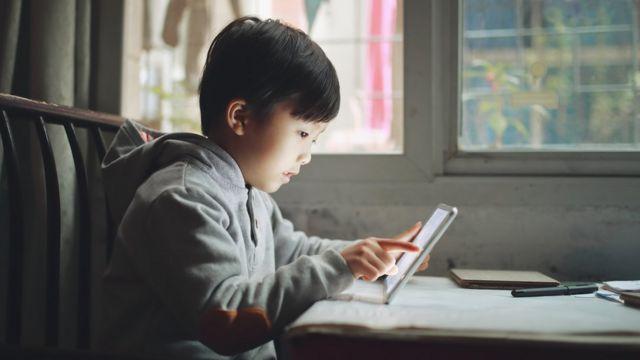 Niño asiático mirando a una tableta en una estancia interior