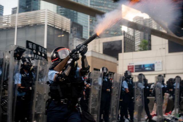 6月12日,一名香港警察正向示威者施放催淚瓦斯。
