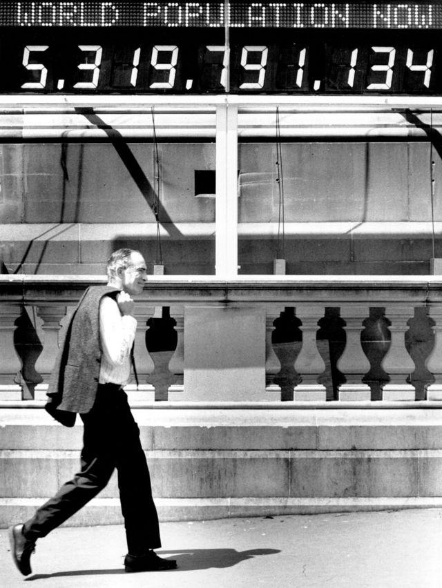 Paul Ehrlich pasea al lado de un contador de población en Australia en 1991.