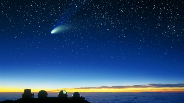 Cometa cruzando o céu e estrelas visíveis ao fundo