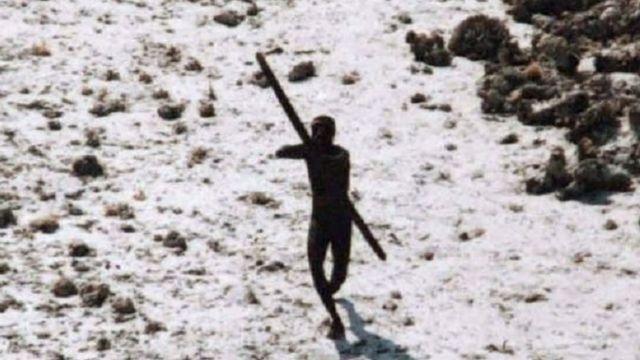 Membro da tribo sentinela mira em helicóptero