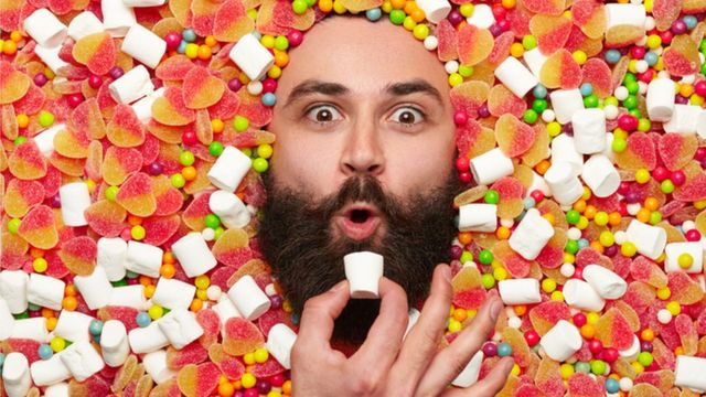 Imagem de rosto de homem rodeado de balas e coisas doces